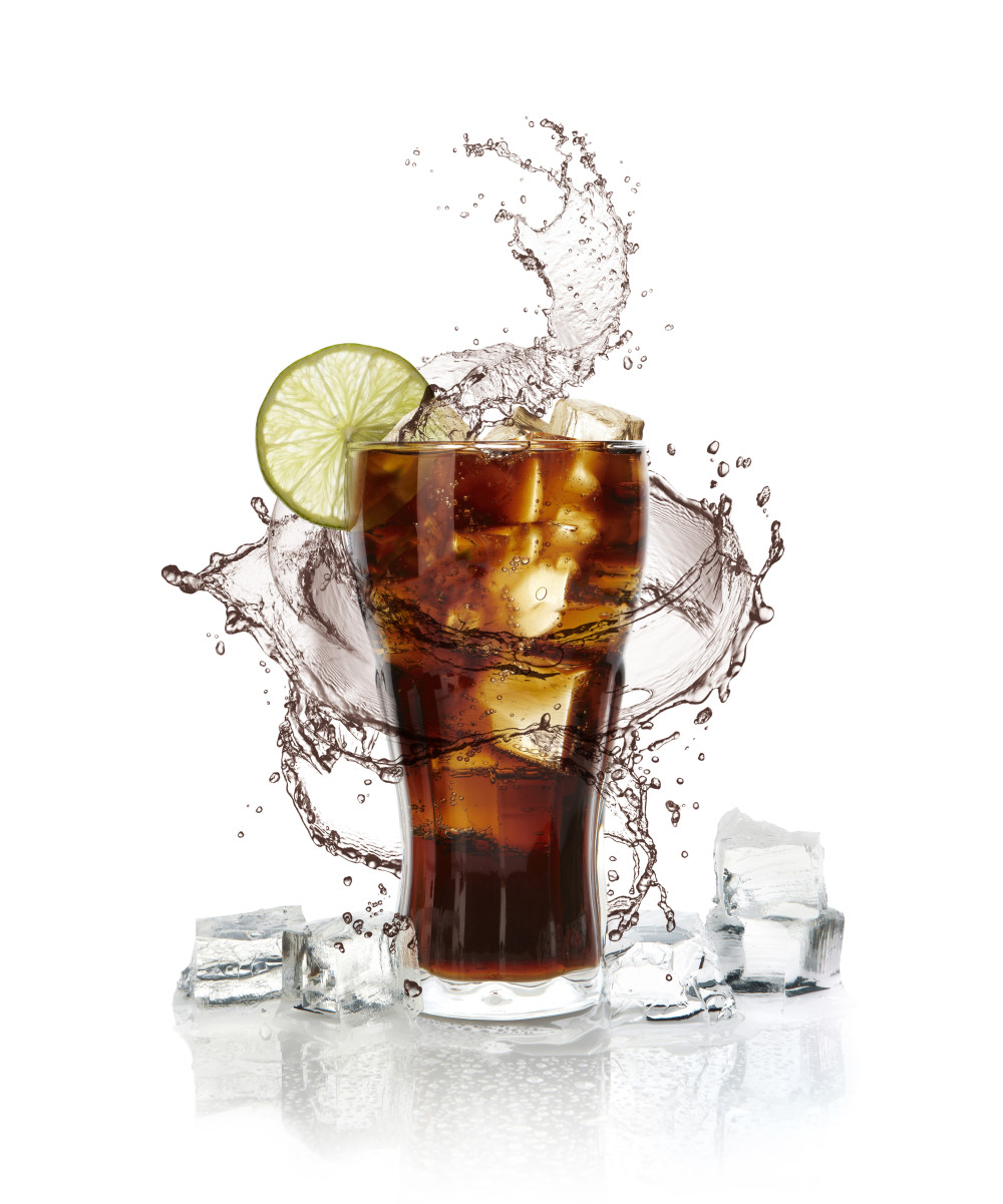 Glass of cola on white background with splash.